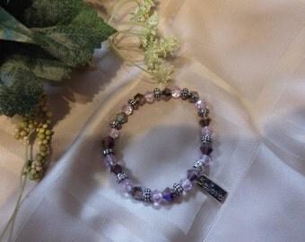 Lavender beaded stretch bracelet with Believe charm