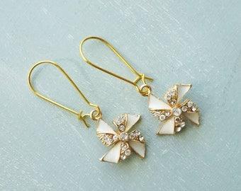 Earrings, gold and white rhinestone pinwheel dangle earrings.