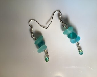 Different shades of light blue seaglass wire wrapped with tiny blue-green bead hanging from them on sterling silver earwires.