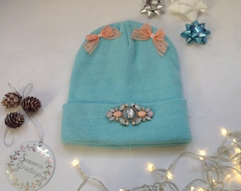 Baby blue wooly hat with gems and bows.