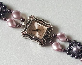 Rectangular watch with a pink face and pink crystals and a band of rosaline, burgundy, mauve, and iridescent purple Swarovski crystal pearls