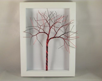 Red and Black copper wire tree in a white wooden picture frame