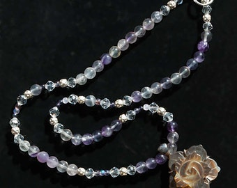 Necklace with silver colored, purple toned and transparent.