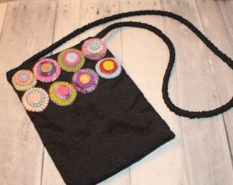 Black cross body bag with wool penny embellishments of various colors