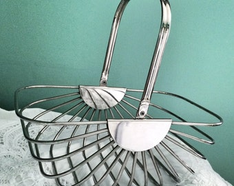 Modern Mid Century metal wire basket polished silver plating with a swinging handle.                          Made by Godinger.
