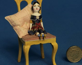 1/12th scale miniature doll on chair with cushion