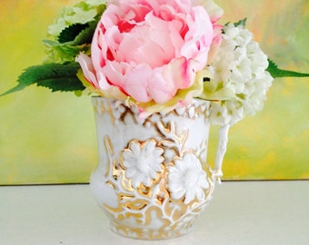Small faux floral arrangement in vintage white/gold pitcher