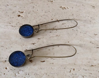 Kidney shaped, navy blue glitter drop earrings.