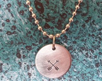 Friendship: Aluminum disc pendant with stamped crossed arrows design on silver-plated chain