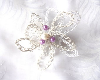 brooch flower , silvery wire and textile threads, one white pearl , purple pearls , silvery support .