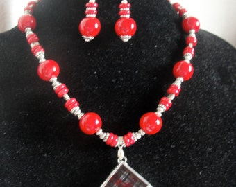 A bold red beaded necklace. Has big glass beads and antique silver beads. Perfect for dressing up and work attire.