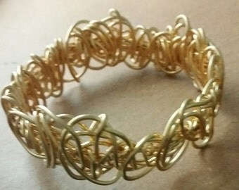 Braided bracelete done from wires covered with gold