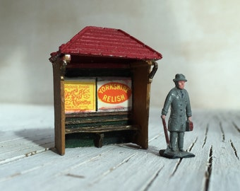 Waiting: A miniature City Gent waits at a bus stop. Vintage die cast figure and bus stop. Miniature toys pieces circa 1930/50s.
