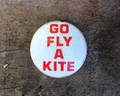 Fly a Kite -- A snide vintage pin urging onlooker to pursue useless recreational pastime