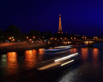 Color Fine Art Photography Print of the Eiffel Tower, Paris France at night with passing boat on the Seine River