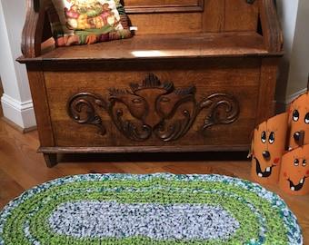 oval crochet rag rug, green white and purple tones.