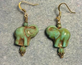 Green Czech glass elephant bead dangle earrings adorned with green Czech glass beads.