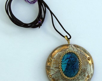 Gold round pendant with blue abalone shell.