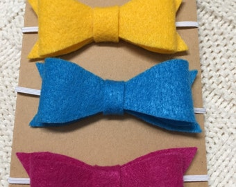 Set of three felt headbands-mustard yellow, bright blue, and magenta.