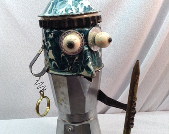 Coffee pot man, has it all , head is metal cup with pour spout, lid, enormous pencil, earring, blood shot eyes.