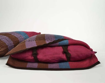 Handwoven cushion of linen. Weaving many-coloured, mauve, brown, blue and raspberry. One of a kind and original weaving.