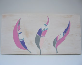 Feathers on white, pink, gray, purple wooden frame