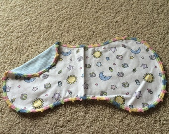 A sun, mooon, and stars burp with blue check on the back.  Pastel edging.