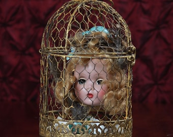 Songbird. Mixed-media, assemblage, vintage doll head, bricolage