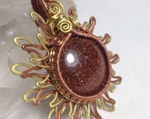 Hand hammered and woven Goldstone Sun or Flower pendant