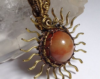 Orange Aventurine sphere in a brass and copper sun wrap, pendant