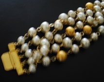 Runway vintage 80s gold tone metal wide bracelet with a 5 twisted strand of  white pearl and textured metal beads. Made by St.John.Size 7.