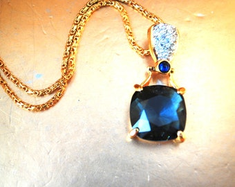 Luxurious vintage 80s gold tone metal necklace with a mod style pendant: clear rhinestones a navy blue crystal. Made by Swarovski.