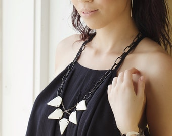 Triangular piece necklace with criss cross chains