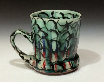 Red white and blue striped mug with black circles and copper glaze.