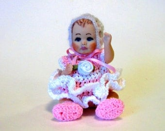 "Baby doll 4"" cast in porcelain from a vintage mold wearing a pink crocheted dress"