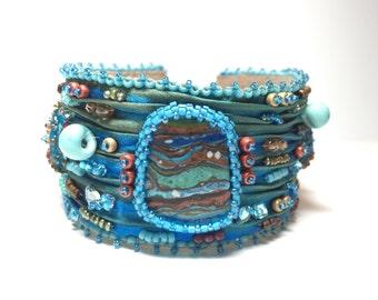 Shibori silk cuff bracelet with Rainbow Calsilica cabochon