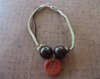 Green and Brown Leather Bracelet with Brown Wood Beads and Stamped Terra Cotta Charm