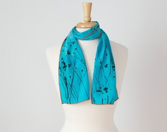 smaller turquoise teal hand painted silk scarf with native sunflower print and orange edges