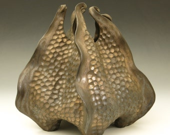 Porcelain urchin vessel with curlicues in bronze glaze, hand carved