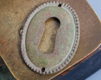 Antique miniature brass key hole escutcheon