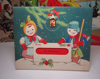 1940's WB die cut embossed peek thru christmas card dressed up snowman holding a shovel,snow lady in apron standing in snow w/ giant letter