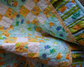 Traditional baby quilt  in a modern fabric collection, barnyard critters. Aqua and yellow farm animals quilt.