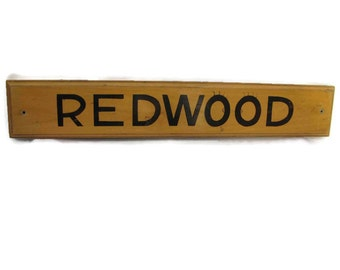"""vintage wooden sign says """"REDWOOD"""" in solid wood with black lettering."""