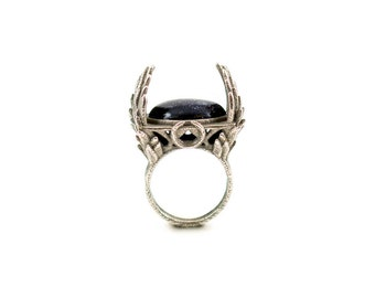 The Witch's Ring - An enchanting ring with sprays of feathers engulfing a Goldstone gemstone.