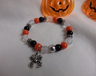 Halloween stretch bracelet with orange, black and clear beads and silver spacers with spider charm