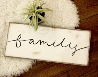 Cursive family in black and white rustic wood sign