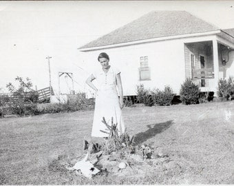 A found vintage photograph of a woman standing in front of her cacti garden on an apparently hot day