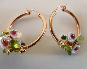 Flora Earrings are dainty rose gold hoops wired with bouquets of rubies, pearls, emeralds, and peridot leaves, and scattered gold beads.