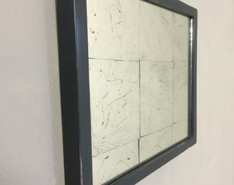 Pewter bole frame with reverse glass gilding (verre eglomisé), on charcoal background