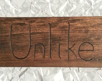 UNLIKE - a wood-burned sign of disdain